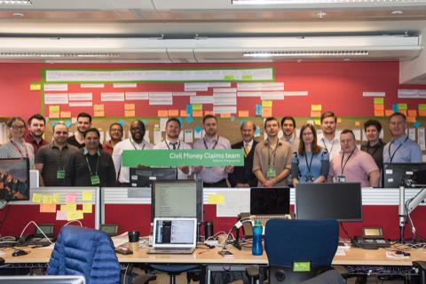 group of people standing behind desks