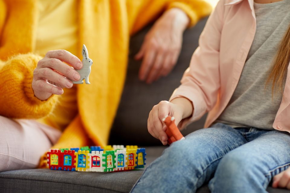Adult sitting with child on sofa playing with toys - no faces shown