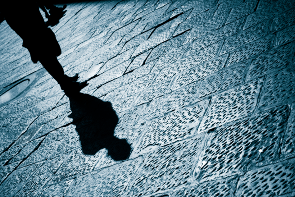 A photo of someone shadow walking down pavement on dark street