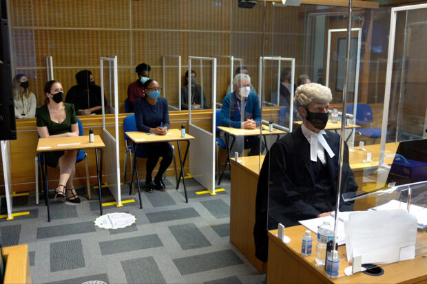 Photo of a mock trial with the barrister and jury members behind screens and wearing facemasks