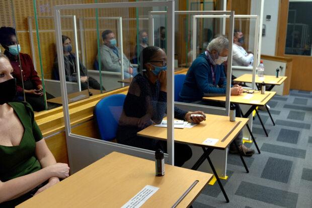 Members of the jury in a mock trial sitting between plexiglass screens and wearing masks