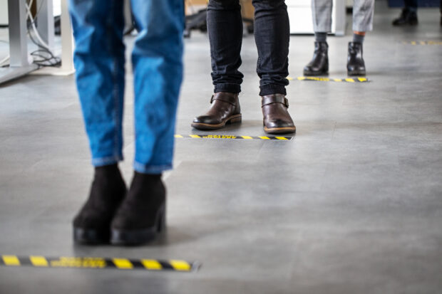 Image of people's feet in a socially distanced queue