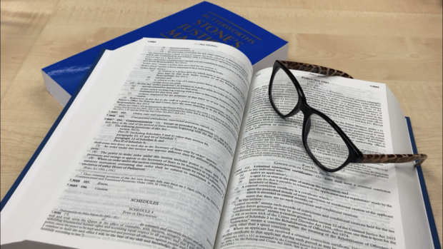 Image of a legal publication open with glasses on the side